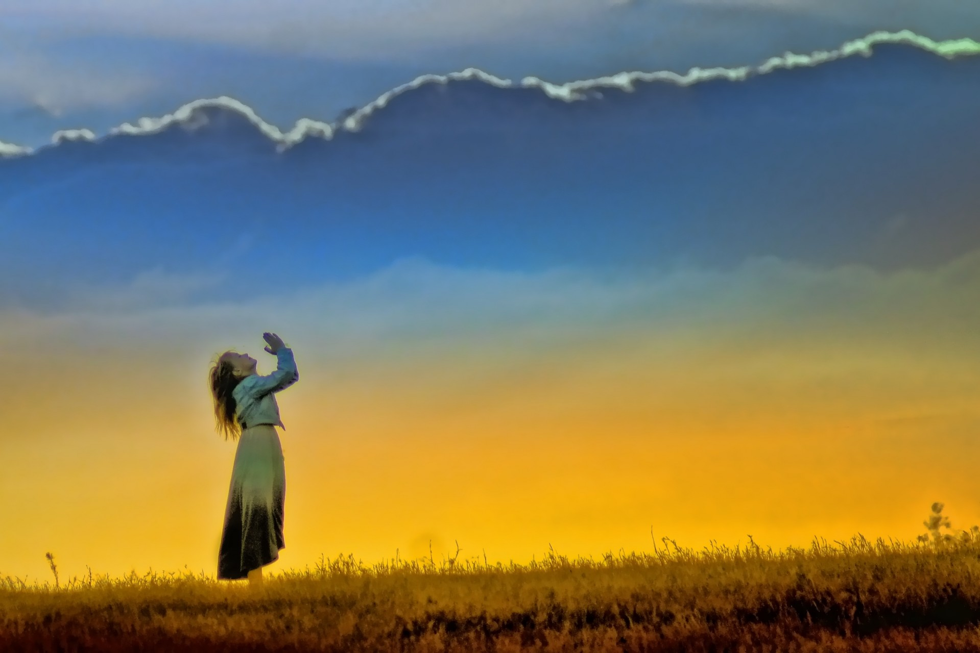 Woman praying in the sunset